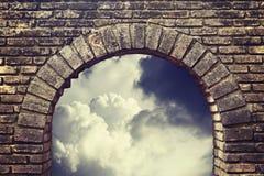 Cielo del fondo que mira a través de una ventana vieja del ladrillo Imagen de archivo