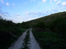 Cielo della primavera e strada della montagna Fotografie Stock