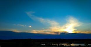 Cielo di tramonto con la siluetta di treeline immagini stock