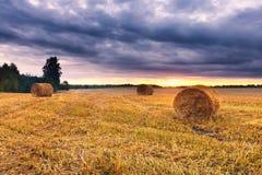 Cielo di tramonto sopra il campo con le balle della paglia Fotografie Stock