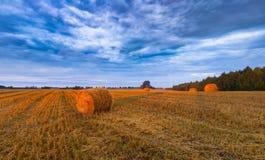 Cielo di tramonto sopra il campo con le balle della paglia Immagine Stock