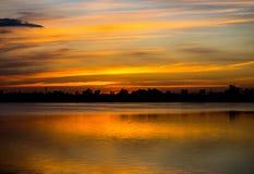 Cielo dorato stupefacente di tramonto con la riflessione sul lago calmo Immagine Stock