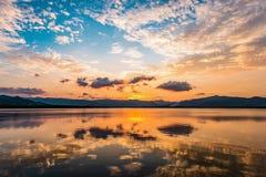 Cielo dramático de la puesta del sol refecting a la superficie del agua plana imagen de archivo