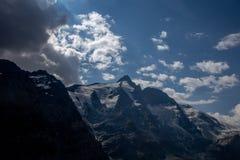 Cielo dramático en un valle con una montaña Grossglockner imagen de archivo