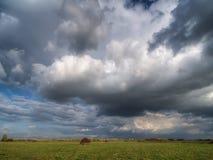 Cielo dramático sobre un campo con un pajar imagen de archivo