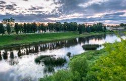 Cielo drammatico di tramonto sopra il fiume di Tvertsa e le sue rive pittoresche dopo la tempesta Città provinciale russa Toržok, Fotografie Stock