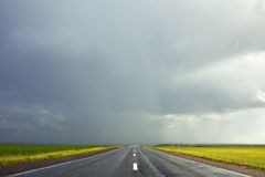 Cielo e nuvole tempestose scure e una strada bagnata nella pioggia Immagini Stock