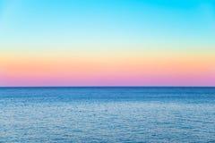Cielo en colores pastel con un mar tranquilo debajo Fotos de archivo libres de regalías