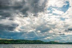 Cielo encendido dramático con los rayos a través de las nubes sobre un pequeño lago foto de archivo