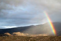 Cielo enorme por completo de nubes con el arco iris minúsculo sobre las montañas de Santa Catalina en Tucson, Arizona Foto de archivo libre de regalías