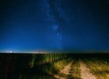 Cielo estrellado de la noche sobre la carretera nacional en campo y campo verde Imagenes de archivo