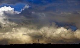 Cielo hermoso con las nubes volumétricas durante puesta del sol y bosque Fotografía de archivo