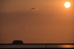 Cielo llano anaranjado con la pequeña nube de la puesta del sol la cuarta y barra de arena negra del contraste con la tira o agua Imagenes de archivo