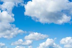 Cielo luminoso blu di estate con le nuvole lanuginose un giorno soleggiato immagine stock
