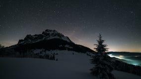 Cielo nocturno con las estrellas que se mueven sobre pico de montaña en lapso de tiempo de la astronomía del invierno almacen de metraje de vídeo
