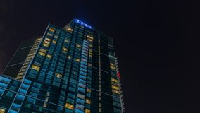 Cielo nocturno con las nubes sobre rascacielos moderno con el timelapse de la arquitectura de las ventanas que brilla intensament metrajes