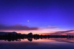 Cielo nocturno hermoso con las estrellas, las nubes y las reflexiones en el wa