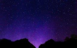 Cielo notturno con il lotto delle stelle brillanti con il fondo vago della montagna Fotografia Stock