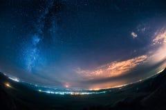 Cielo notturno e Via Lattea sopra una città luminosa Immagine Stock Libera da Diritti