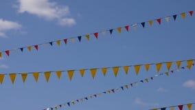 Cielo nublado azul con las banderas coloridas del partido para el carnaval Placa del fondo, fondo video dominante de la croma almacen de video
