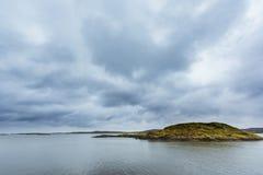 Cielo nublado con una isla Imagenes de archivo
