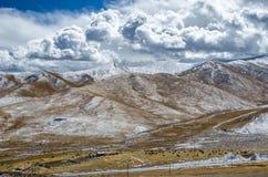 Cielo nublado tibetano asombroso y montañas nevosas de la mucha altitud Fotografía de archivo