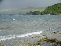 Cielo nublado y arco iris sobre la isla tropical fotos de archivo libres de regalías