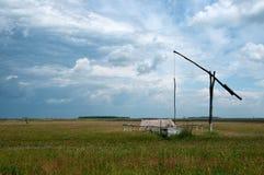 Cielo nublado y prado con el cigoñal Imagen de archivo