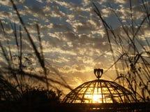 Cielo nublado y sol de la puesta del sol detrás del vidrio de un invernadero viejo fotos de archivo