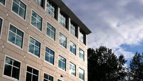 Cielo nuvoloso con la facciata di vetro riflessa illuminata sull'edificio per uffici moderno archivi video