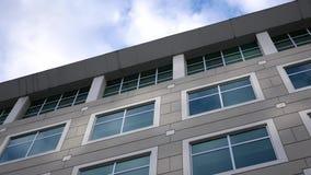 Cielo nuvoloso con la facciata di vetro riflessa illuminata sull'edificio per uffici moderno stock footage
