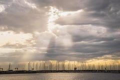Cielo nuvoloso drammatico di tramonto con il raggio del raggio luminoso del sole sopra la barca J Fotografia Stock Libera da Diritti
