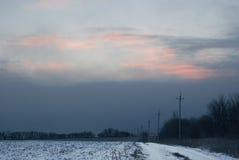Cielo nuvoloso pesante sopra la strada del campo di inverno Fotografie Stock