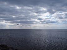 Cielo nuvoloso scuro drammatico sopra il mare fotografia stock libera da diritti