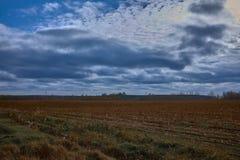 Cielo nuvoloso sopra il campo marrone dopo la raccolta immagini stock libere da diritti