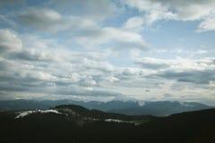 Cielo nuvoloso sopra le montagne Fotografia Stock
