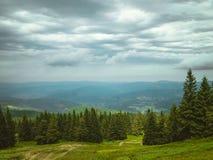 Cielo nuvoloso sopra le montagne immagine stock