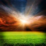 Cielo oscuro de la tarde y campo verde Imagenes de archivo