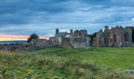 Cielo pesado en la puesta del sol sobre el priorato de Lindisfarne, isla santa Foto de archivo