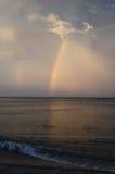 Cielo pintoresco de la tarde con un arco iris sobre el agua oscura de Baikal Foto de archivo