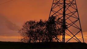 Cielo porpora rosso di tramonto della nuvola del cielo drammatico di tramonto, supporto ad alta tensione del metallo ed albero ba archivi video