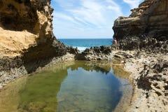 Cielo que refleja en una piscina del agua de mar verde Foto de archivo