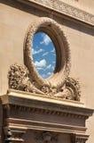 Cielo reflejado en ventana redonda adornada Fotografía de archivo