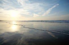 Cielo, reflexiones del sol en la playa arenosa y mar fotos de archivo