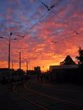 Cielo rojo, tiempo del ocaso Linternas oscuras de la calle, tranvía Foto de archivo