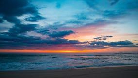 Cielo rojo vivo en la puesta del sol en la playa con las nubes oscuras imagen de archivo libre de regalías