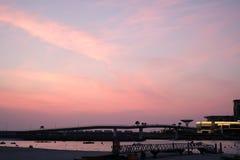 Cielo rosado hermoso de la puesta del sol cerca de la costa con algunas nubes del marshmellow en ella fotografía de archivo