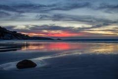 Cielo rosado y de oro de la puesta del sol sobre la playa aislada fotos de archivo libres de regalías