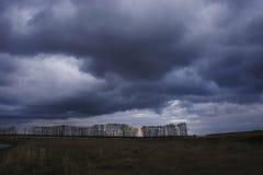 Cielo scuro e blu scuro sui precedenti del campo di autunno con gli alberi umore ed atmosfera freschi di tristezza Fotografie Stock Libere da Diritti