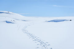 Cielo soleado claro con las pistas del esquí en un paisaje del invierno en montañas nevadas Imagenes de archivo